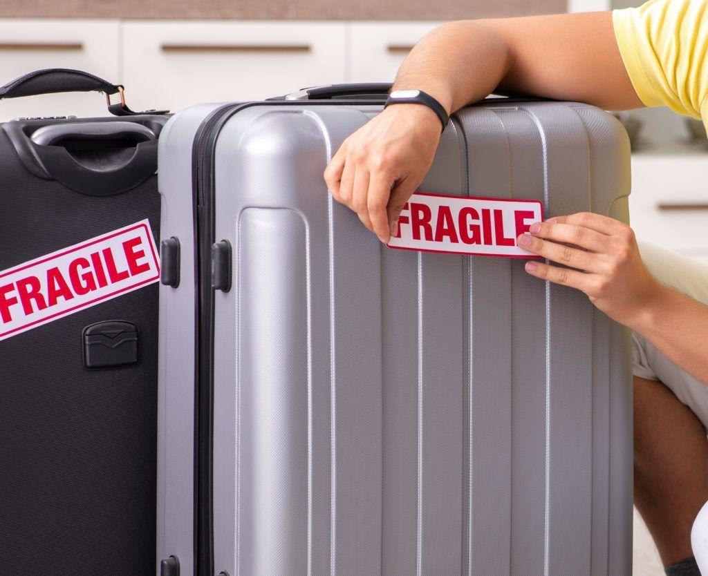 """Hombre colocando """"Frágil"""" pegatinas en sus maletas"""