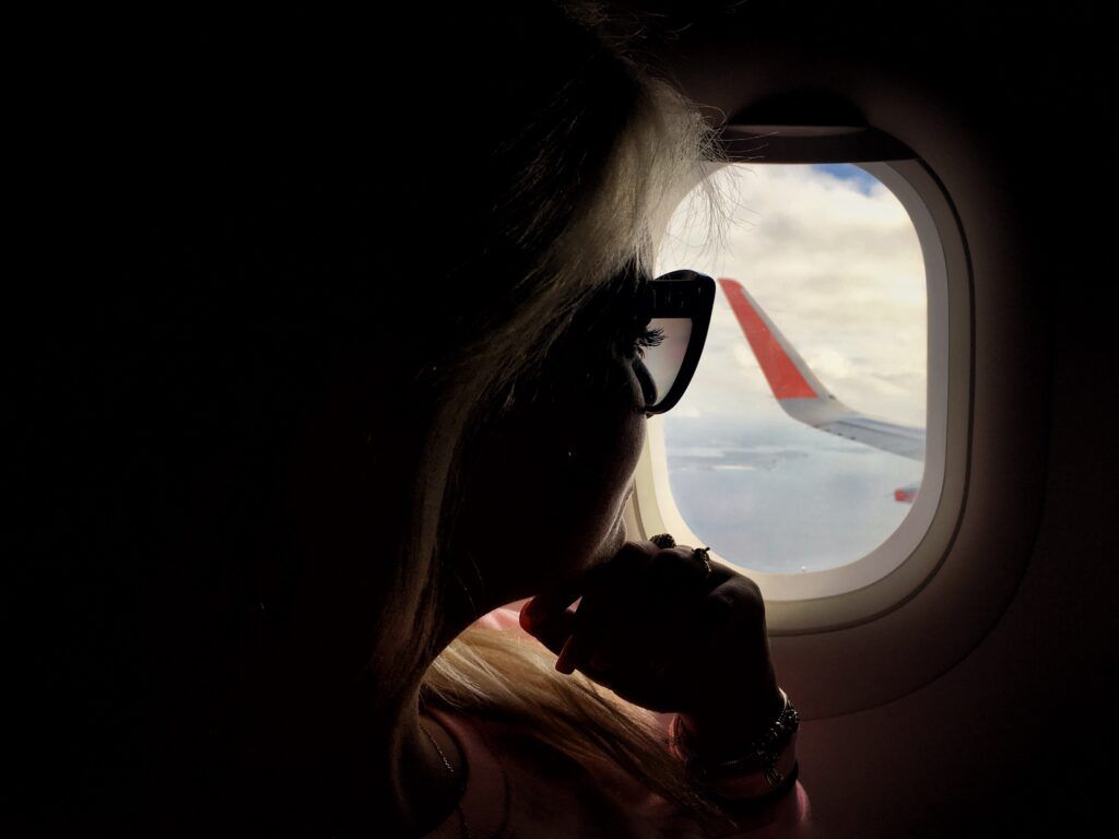 1632435428 80 a millennial girl sitting by the window on an airplane while traveling t20 mo407m